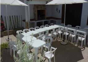 Mesas y sillas junto a la barbacoa de la casa rural
