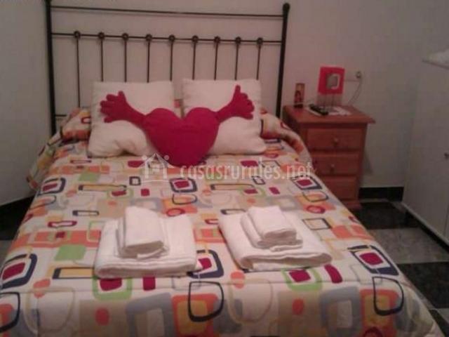 Dormitorio de matrimonio con toallas blancas sobre la colcha