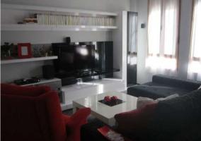 Sala de estar de la casa con sillones tapizados y televisor de plasma