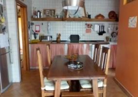 Cocina con mesa de madera y azulejos en blanco