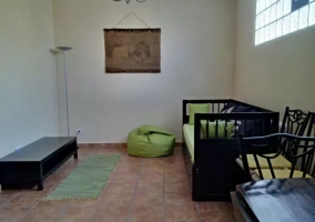 Sala de estar con sillones y ventanales
