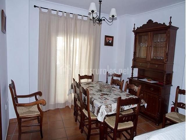 Comedor con mesa de madera y mueble con copas