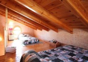 Dormitorio abuhardillado con varias camas y techos de madera