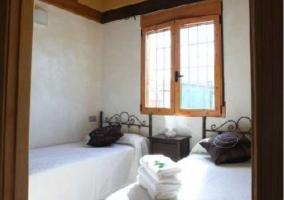 Dormitorio doble con colchas en color blanco y ventana