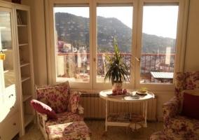 Sala de estar con sillones tapizados y ventanales