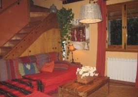 Salón con sillón en L y escaleras al primer piso