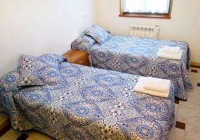 Dormitorio doble con camas separadas por la mesilla