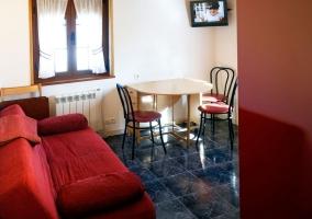 Sala de estar con sillones en rojo y mesa junto a la tele