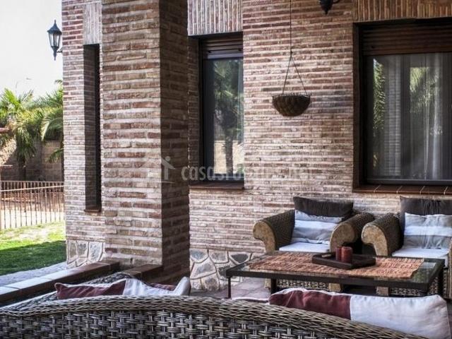 Vistas del porche con muebles y jardines