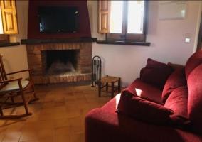 Sala de estar con sillones en burdeos y una chimenea con la tele