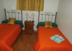 Dormitorio doble con colchas naranjas