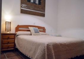 Dormitorio de matrimonio con cabecero de madera y mesillas