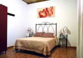 Dormitorio de matrimonio con cuadro de flores y mantas