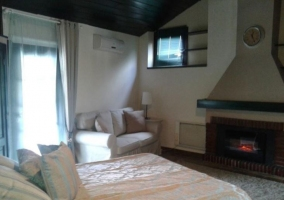 Dormitorio con cama frente a la chimenea