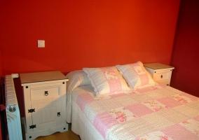 Cama de matrimonio con dos mesillas de noche y pared roja