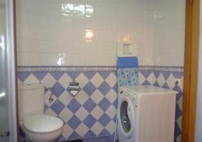 Detalle del sanitario y la lavadora en el cuarto de baño