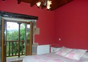 Dormitorio con pared roja y salida a la terraza