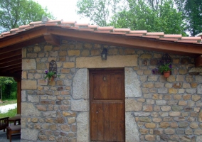 Entrada trasera de madera con pared de piedra