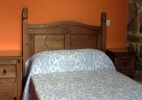Habitación de matrimonio con paredes naranjas y cabecero de madera