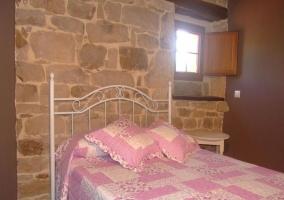 Habitación con edredón rosa y pared de piedra