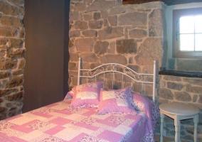 Habitación con edredón rosa y ventana