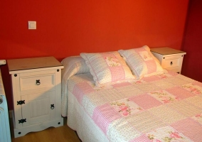 Habitación de matrimonio con pared roja y mesillas blancas