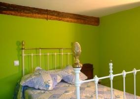 Habitación con paredes verdes y edredón azul