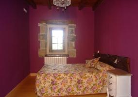 Vista del dormitorio con pared morada y edredón de flores