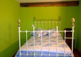 Vista frontal de la cama de matrimonio con pared verde