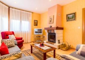Sala de estar con chimenea en piedra y televisor