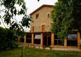 Fachada de casa de piedra con jardín