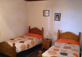 Dormitorio doble con camas individuales y detalles en naranja