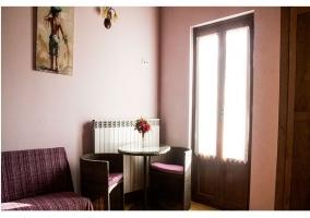 Habitación con cama y sofa y acceso a balcon