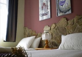 Dormitorio 1, camas, pared de piedra, cuadros