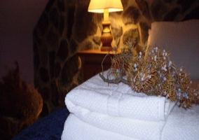 Toallas y detalle de ramo en cama de matrimonio