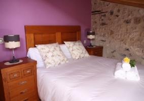 Dormitorio con cama de matrimonio y pared morada