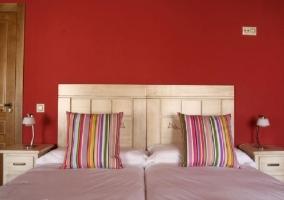 Dormitorio con dos camas individuales juntas y pared de color rojo