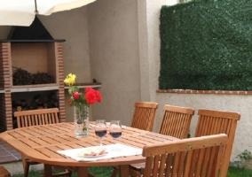 Mesa de madera con sillas alrededor en el patio de la casa