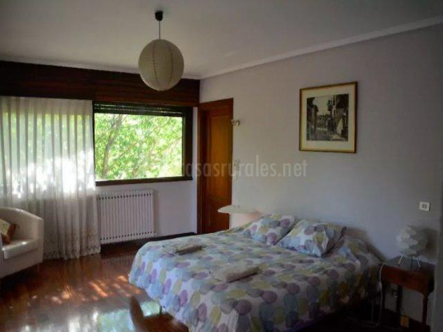Dormitorio con cama amplia y suelos de madera
