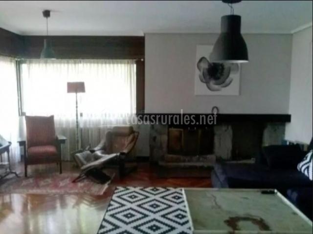 Sala de estar con chimenea y ventanales