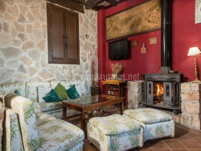 Sala de estar con chimenea encendida y sillones tapizados
