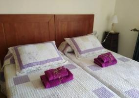 Dormitorio doble con toallas en morado